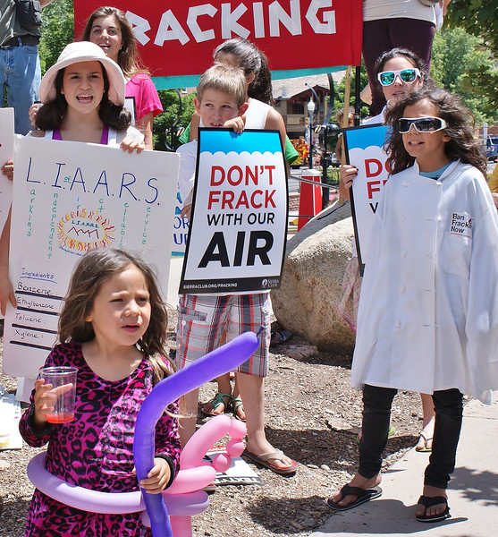 Group of young children hold anti fracking signs at protest, one  young girl with balloon around waste in front.