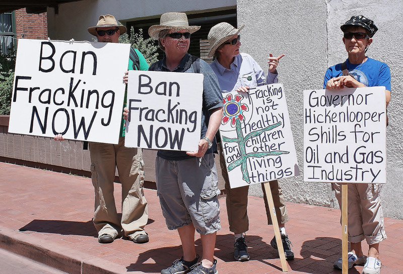 Protesters with anti fracking signs, one directed at Colorado Governor Hickenlooper.