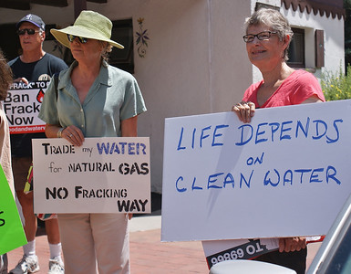 Two women holding signs about water safety at anti fracking demonstration.
