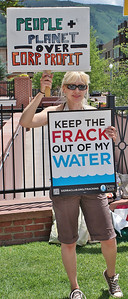 Protester holds signs about fracking and water and corporate profits.