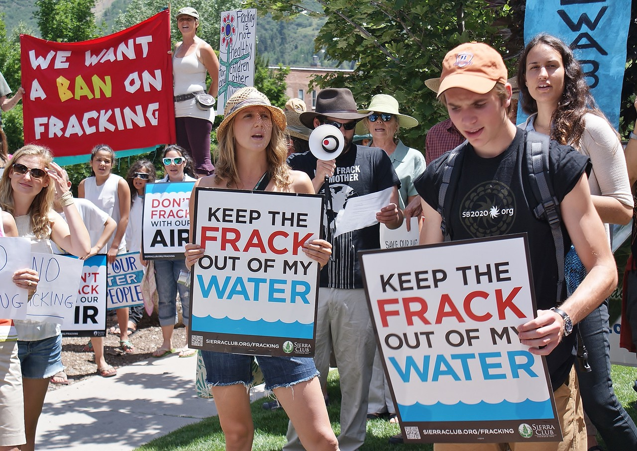 Young man and woman hold signs aboput fracking and water safety at protest, protester behind them with bullhorn, another with ban fracking banner.
