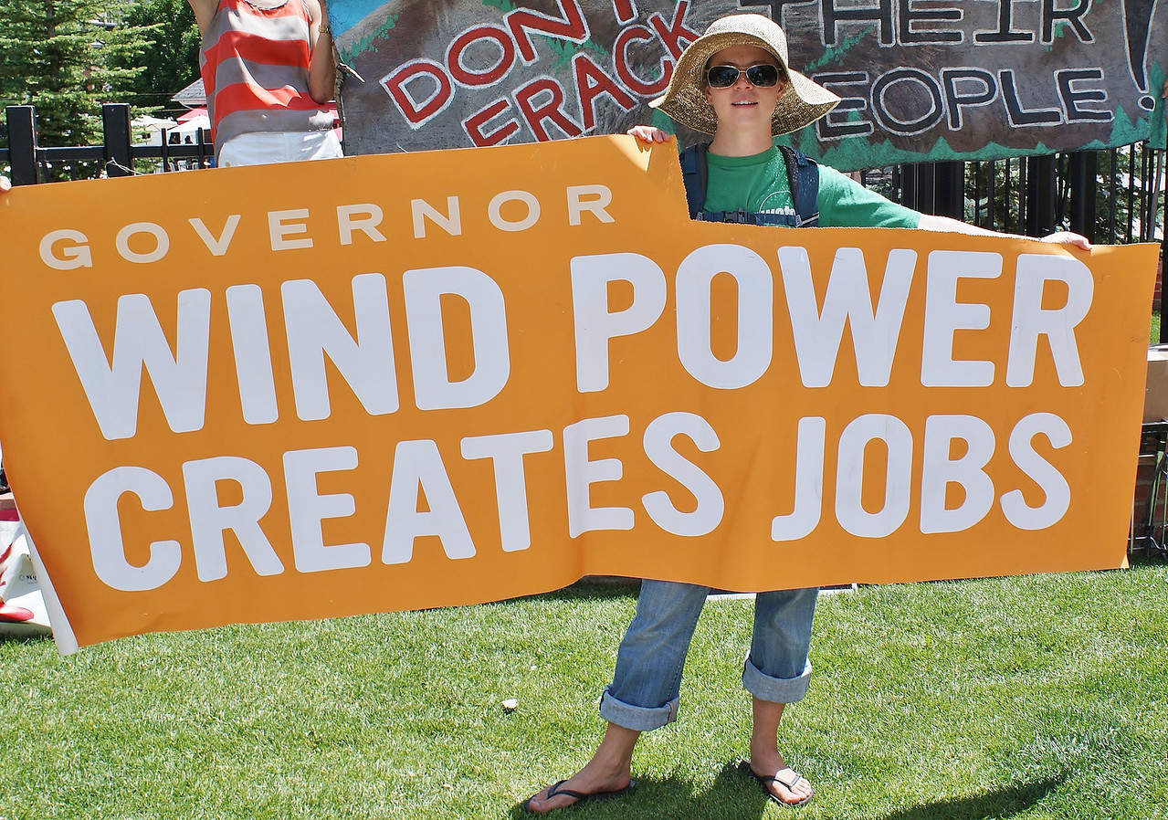"Young woman holds large banner ""Wind Power Creates Jobs"", at fracking protest."