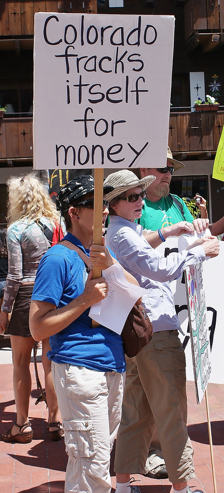 "Woman holds sign ""Colorado Fracks Itself For Money"", at protest."