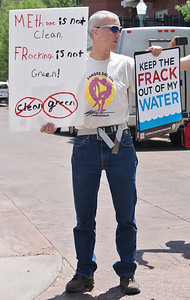 Man concerned with effects of fracking on water safety, holds signs at protest.