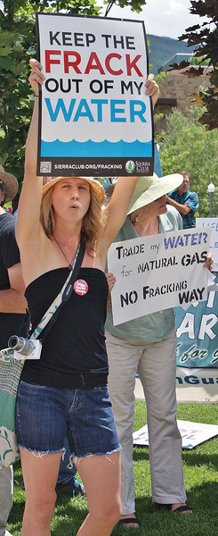 Young woman with sign about water and fracking, another demonstrator behind.