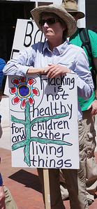 Woman protesting fracking holds sign about fracking not healthy for children.