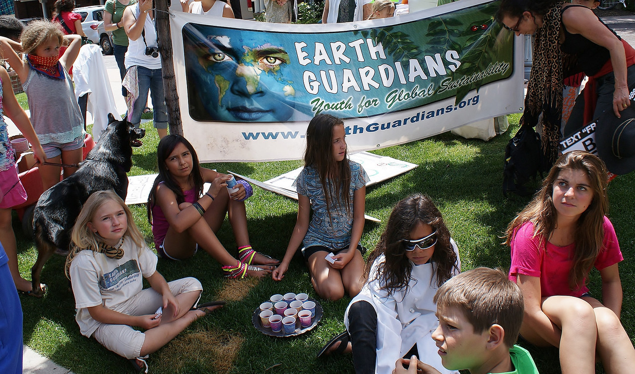 """Group of young girls sitting on lawn in front of """"Earth Guardians"""" banner."""