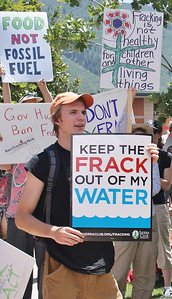 Young man with sign about fracking and water, other protesters with signs behind him.