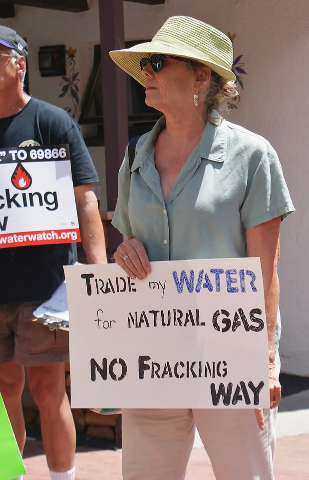 Woman holding sign about water safety at anti fracking demonstration.