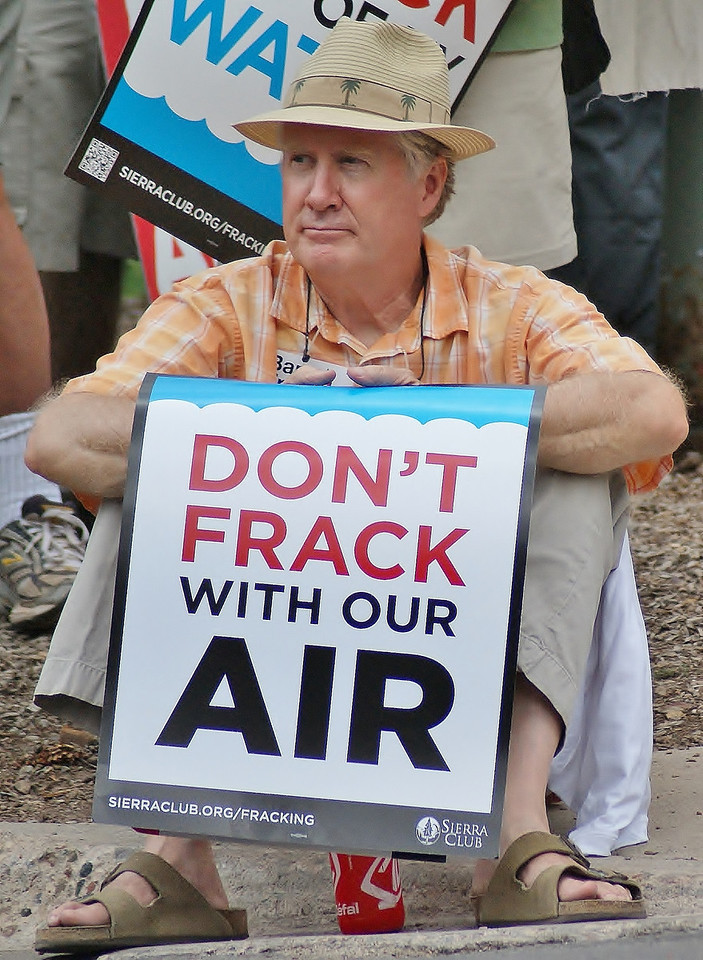 """Man in straw hate with """"Don't Frack With Our Air"""" sign, sitting on curb."""