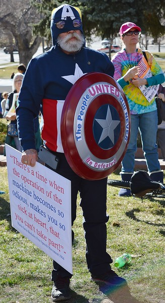 """Man in """"Captain America"""" costume listens to a speaker at an anti-fracking rally at the State Capitol in Denver."""