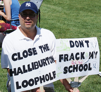 Man in New York Yankees cap holding anti-fracking signs about  fracking near a school and Haliburton