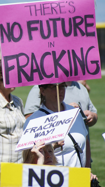 Two women peek out from behind anti-fracking signs they are holding.
