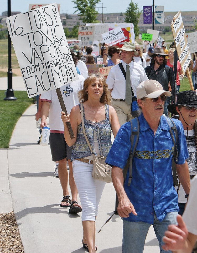 Line of marchers with signs opposing fracking.
