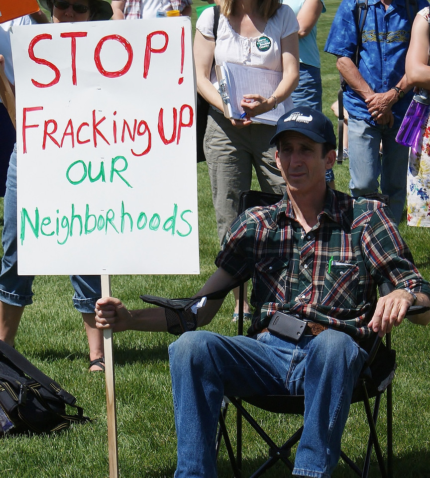 Man sitting in lawn chair holding anti-fracking sign.