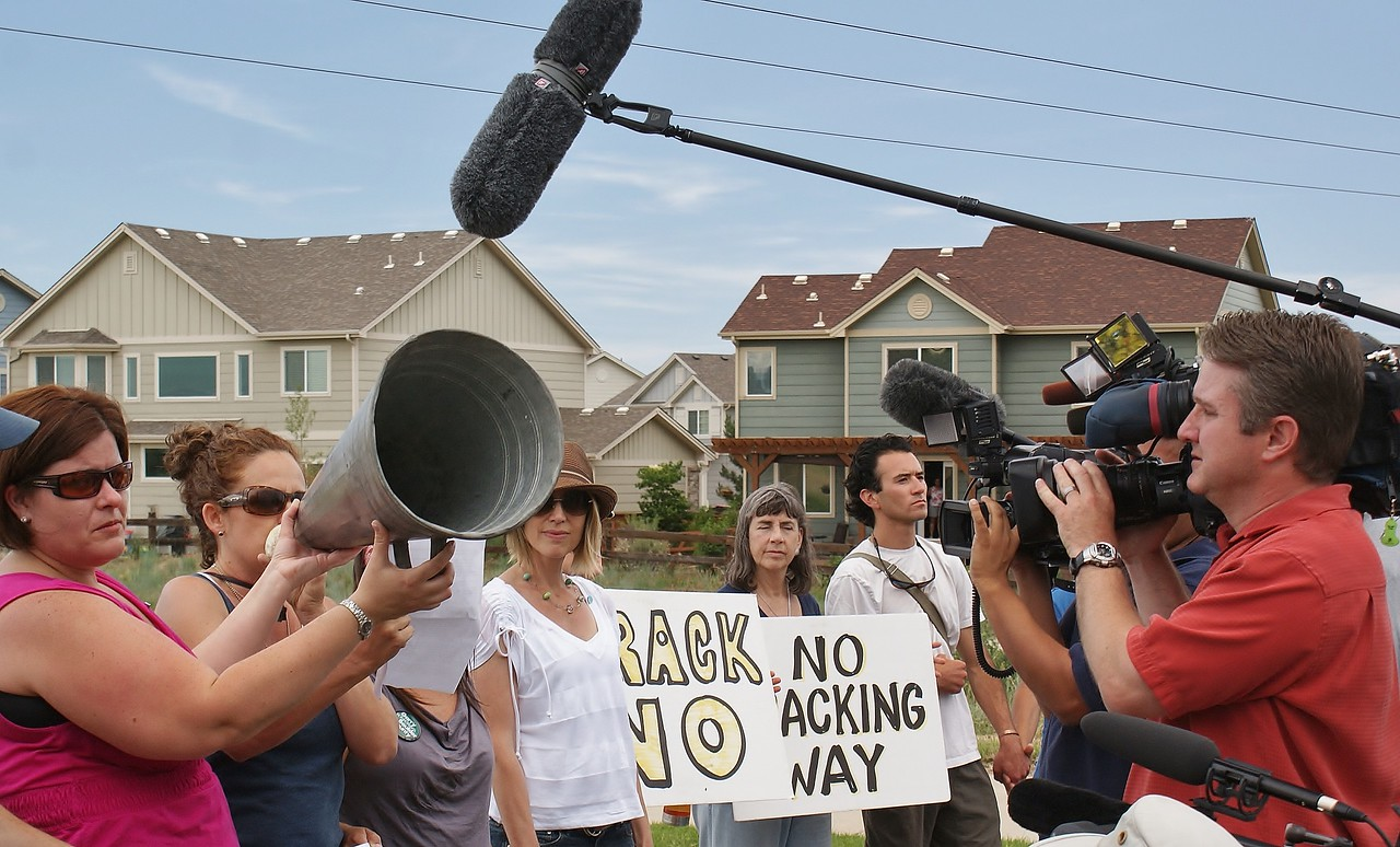 Video camera operator records speaker at a political rally, while woman holds up megaphone for the speaker.