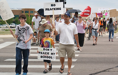 Man and two young sons at the head of long line of marchers protesting fracking.