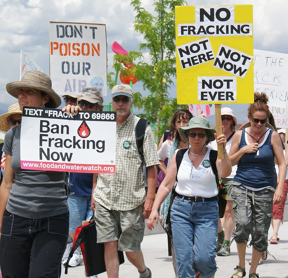 Group of fracking protesters with sign, march together.