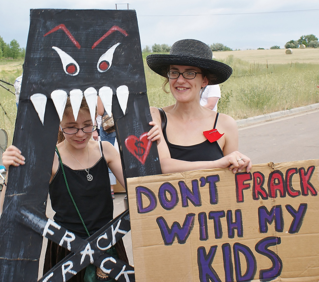 """Woman and young daughter with anti-fracking sign and cardboard """"frack monster""""."""