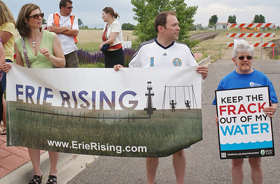 "Anti-fracking protester holding large ""Erie Rising"" banner."
