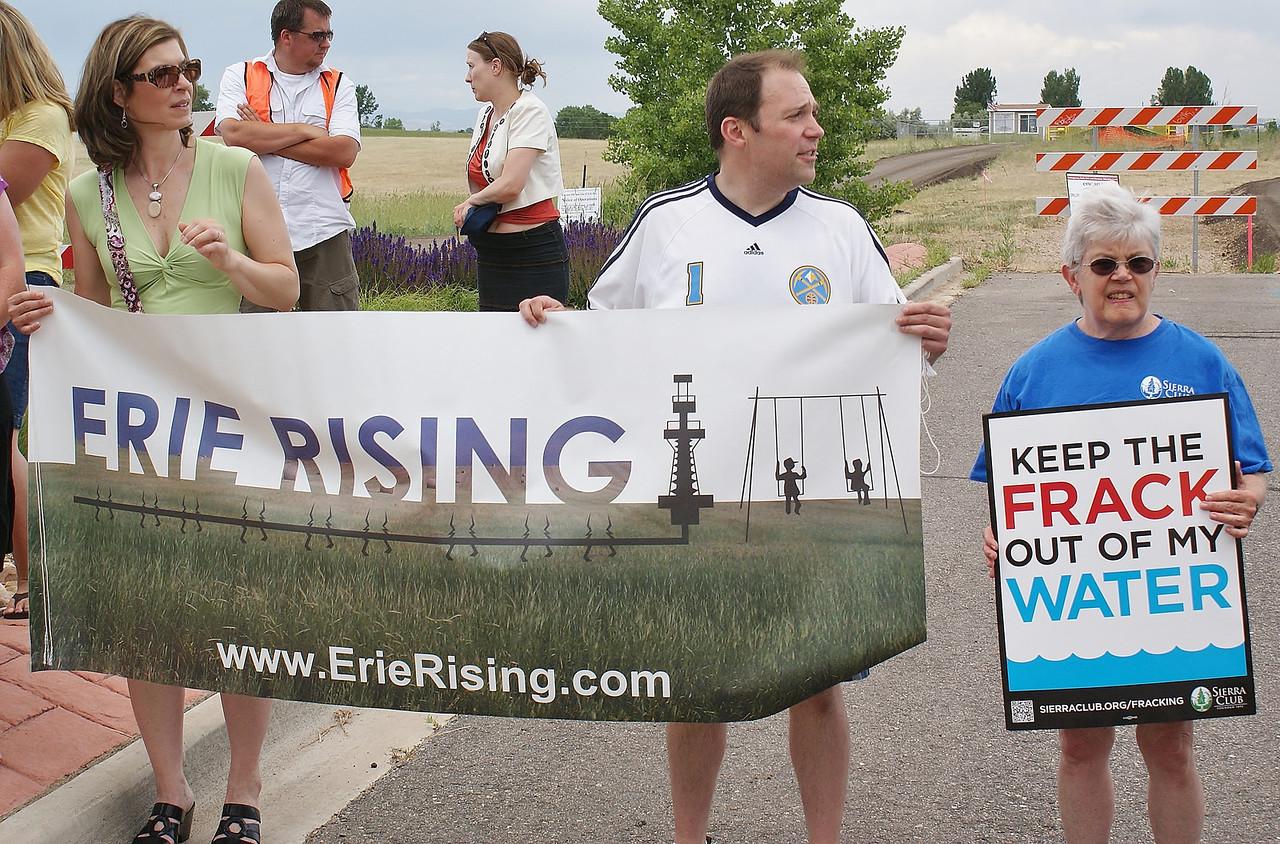 "Anti-fracking protester holding large ""Erie Rising"" banner."