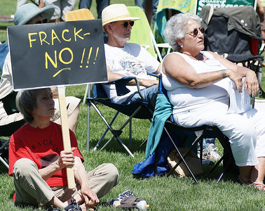 "Woman sitting on lawn holding ""frack no!"" sign, other protesters next to her."
