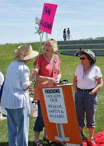 Three women talk with each other, anti-fracking signs next to them.