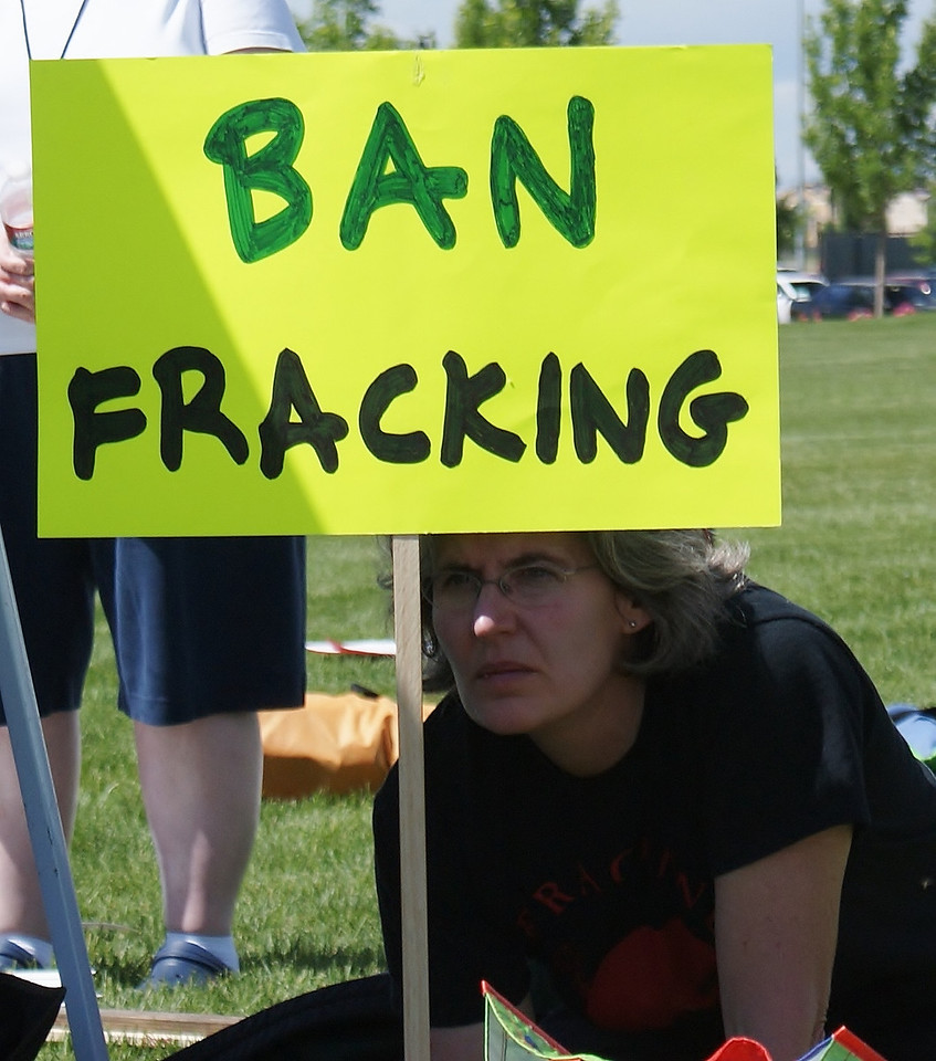 Women looks out from behind anti-fracking sign.