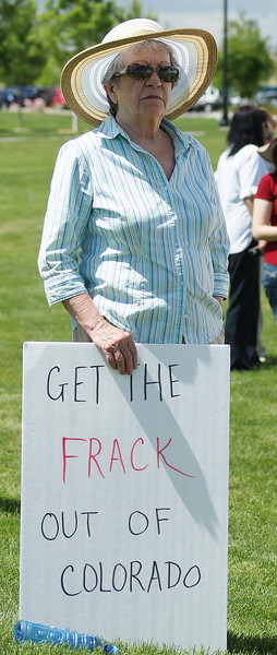 Senior Colorado woman holding sign against fracking in her state.