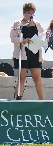 Woman speaks at a microphone on stage, Sierra Club banner below her.