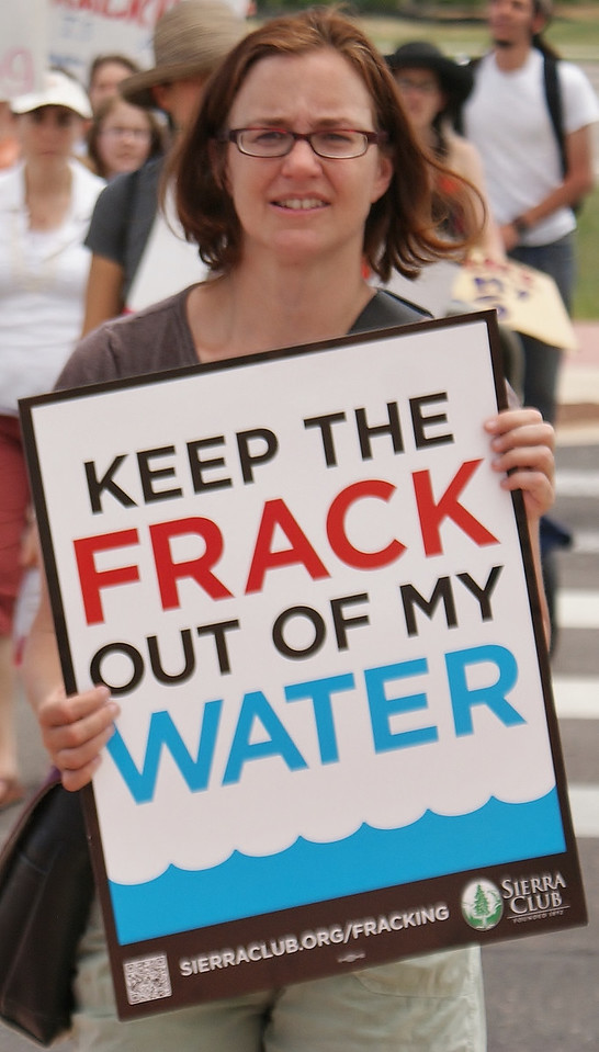 Woman holding sign about fracking and water safety.
