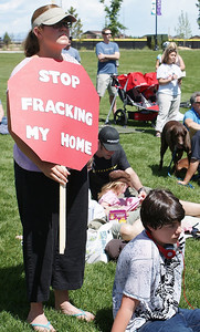 Woman holding stop sign shaped anti fracking sign, other protesters in the background.
