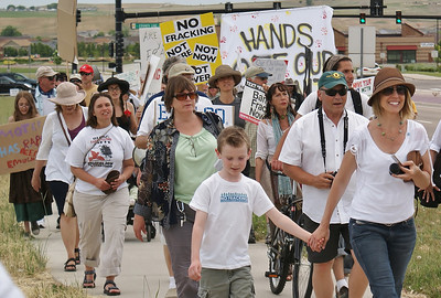 Woman and young son hold hands while marching in anti-fracking protest, many marchers behind them.