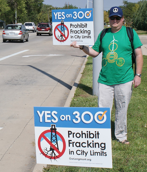 Man standing by side of road with sign supporting anti-fracking ballot initiative