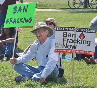 Man sitting on lawn with anti-fracking sign.