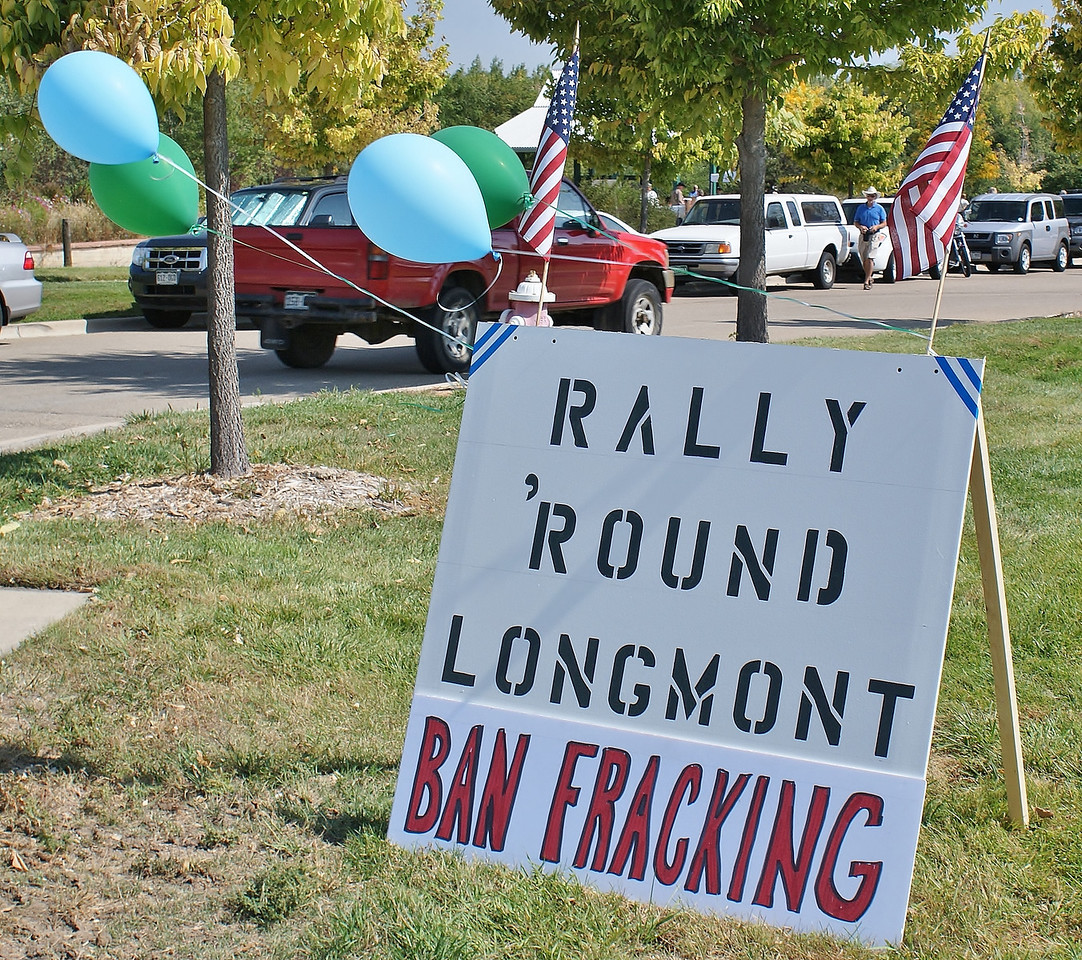 Ban fracking rally sign with balloons and American flag attached, pick-up truck in the background.
