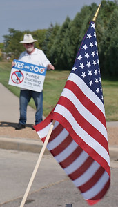Man standing by side of road with sign supporting anti-fracking ballot initiative, American flag in the foreground.