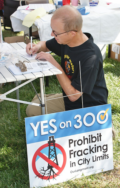 man kneeling at table signing up to support anti-fracking ballot initiative, sign next to table.
