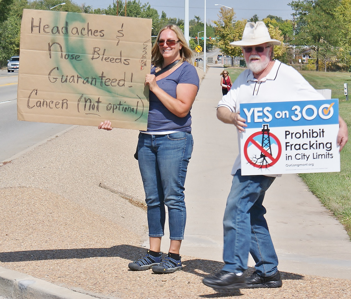 Man and woman standing by side of road with signs supporting anti-fracking ballot initiative.