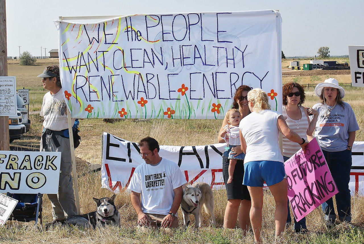 Group of fracking opponents with signs and large banner about renewable energy, standing against fence.