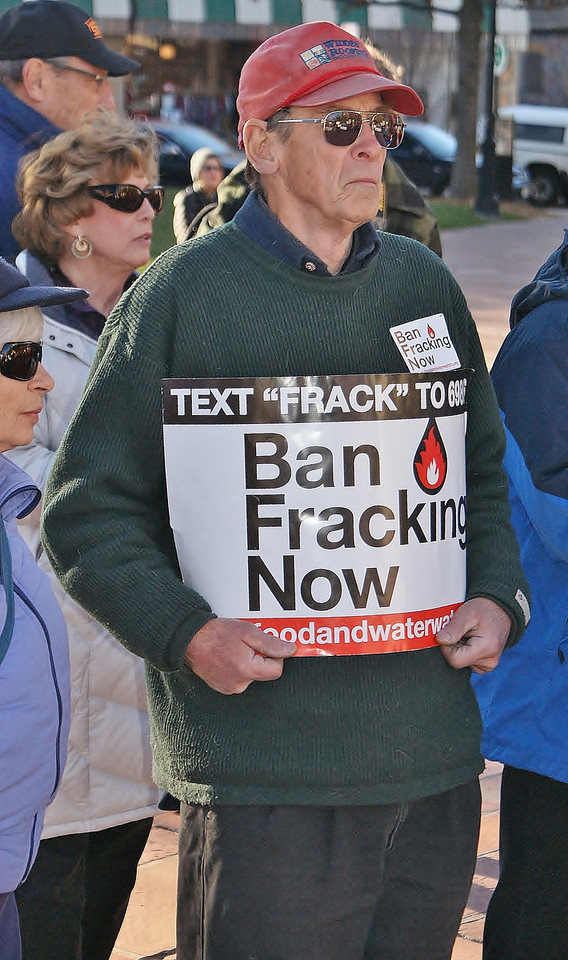 Man holding ban fracking sign at protest.