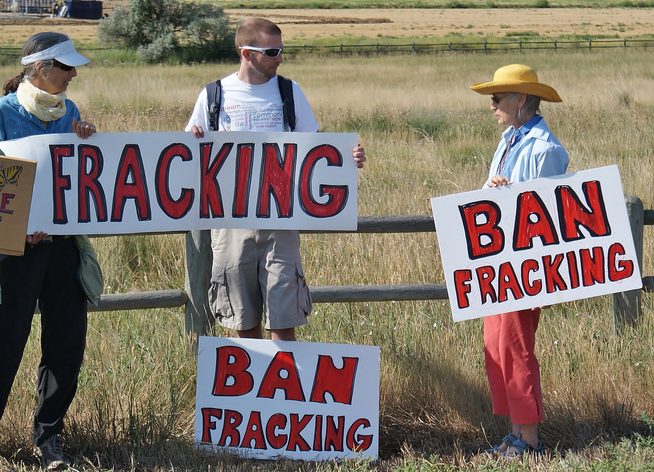 Anti fracking protesters with signs stand against fence at demonstration.