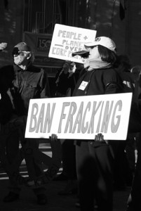 Woman holding ban fracking sign at protest. Black and white photograph.