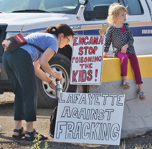 Mother and young daughter at fracking demonstration, protest signs next to them.