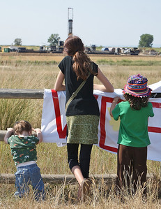 Young girl and two younger children standing against fence, looking at fracking site.