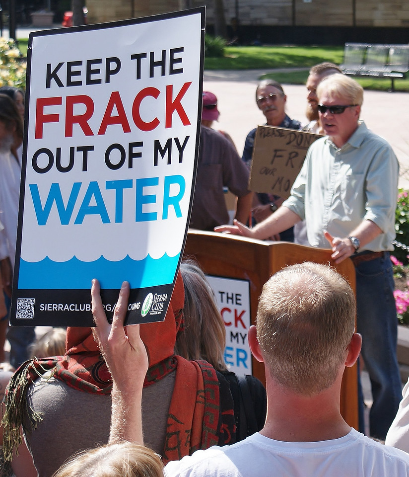 Man speaks from podium at anti-fracking rally, crowd of people listening, in foreground one protester holds sign in the air.