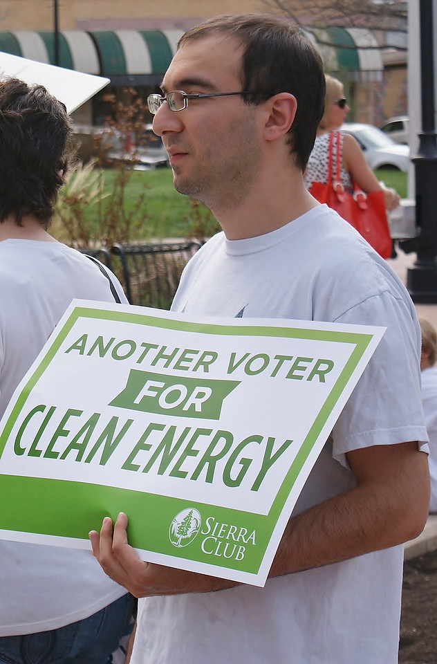 Young man holding sign supporting clean energy.