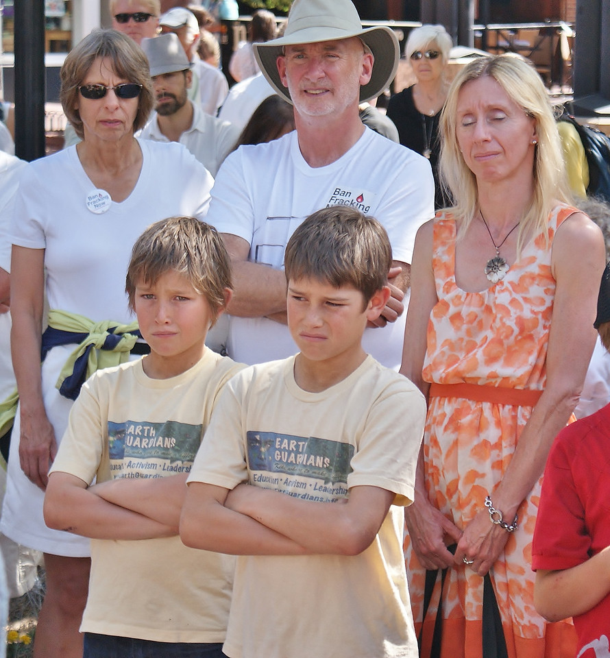 """Twin boys wearing """"Earth Guardians"""" shirts, standing at anti-fracking demonstration, other protesters beside them."""
