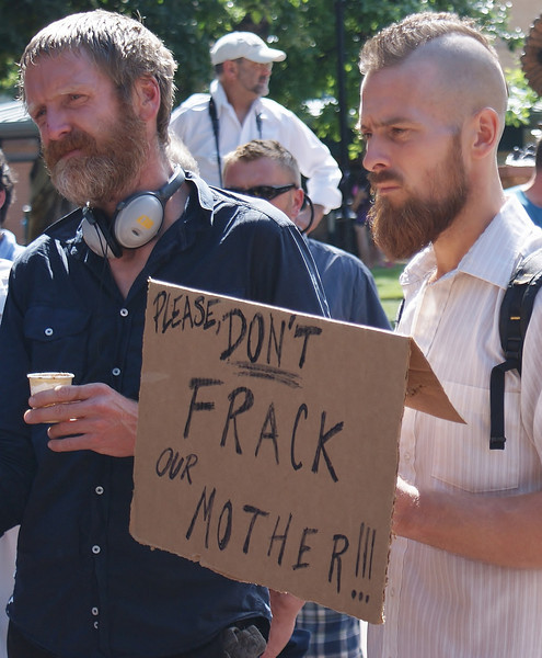 Young man with mohawk haircut holding anti-fracking sign at protest rally.