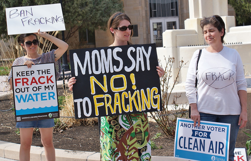 "Woman in brightly colored dress holds sign, ""Moms Say No To Fracking"" at demonstration, other protesters beside her."